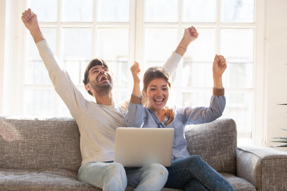 A couple celebrates being debt-free while sitting on their couch