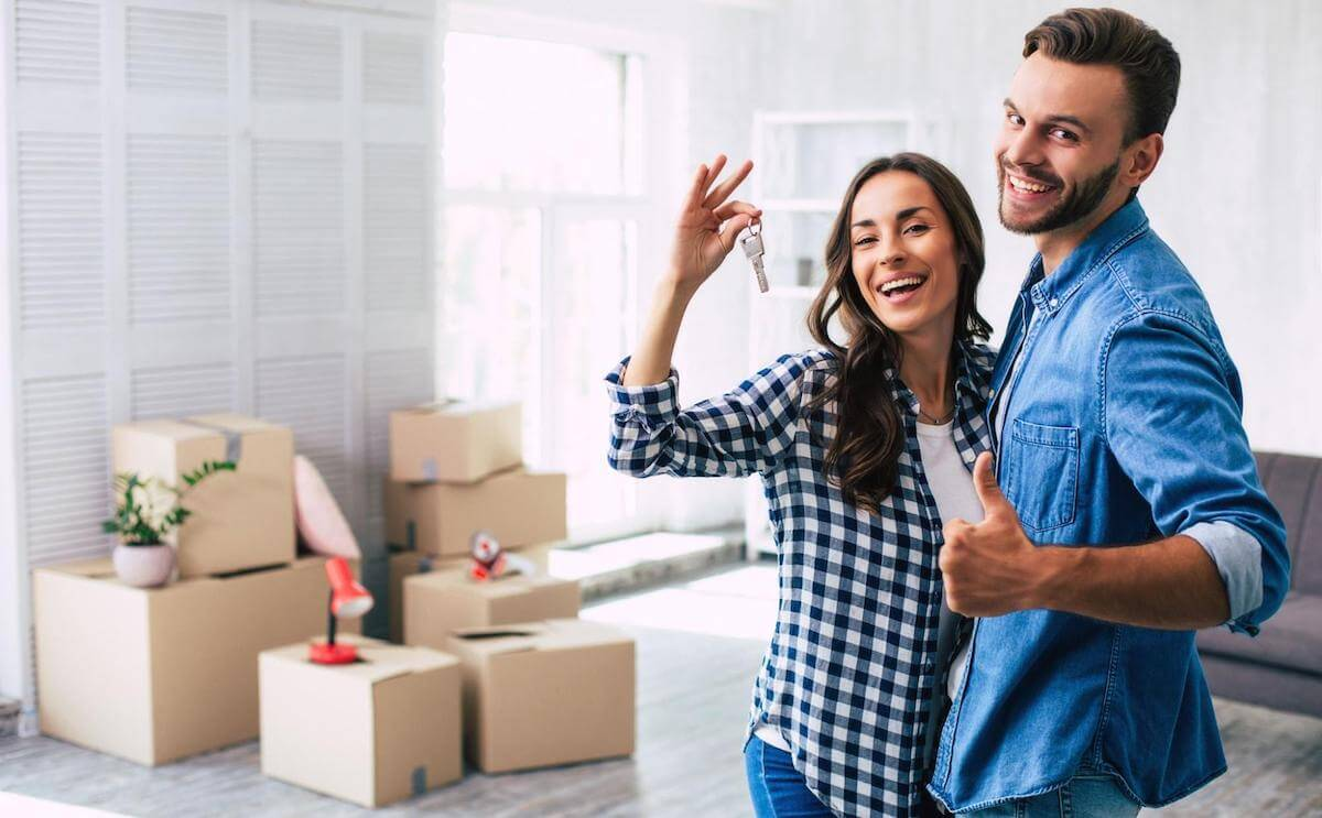 A smiling couple holds up the keys to their new home