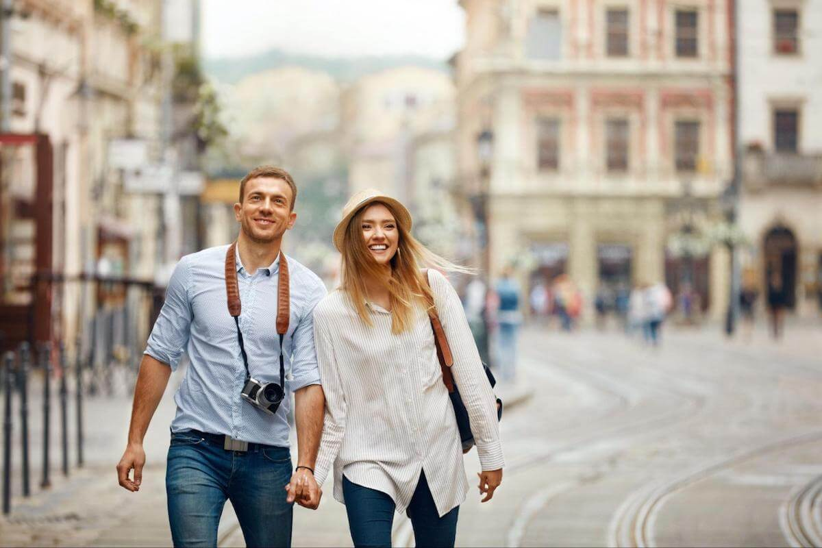 A smiling couple goes sightseeing while traveling