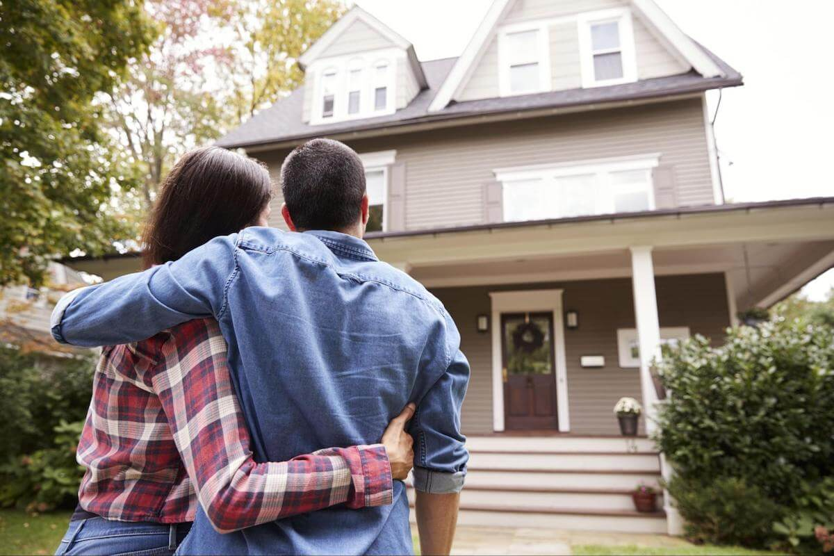 Debt to income ratio for mortgage: A couple stands outside looking at their new home.