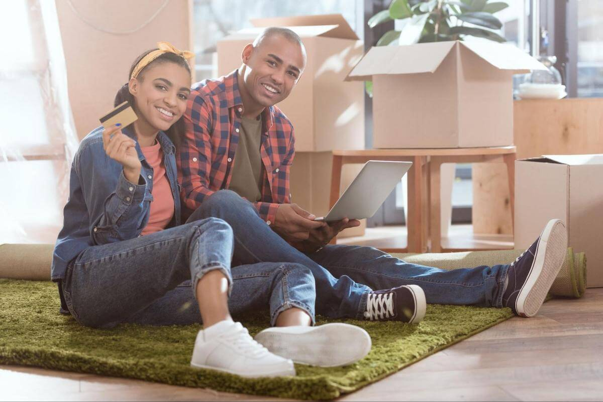 A smiling couple uses their credit card and a laptop while sitting on the floor of their new home