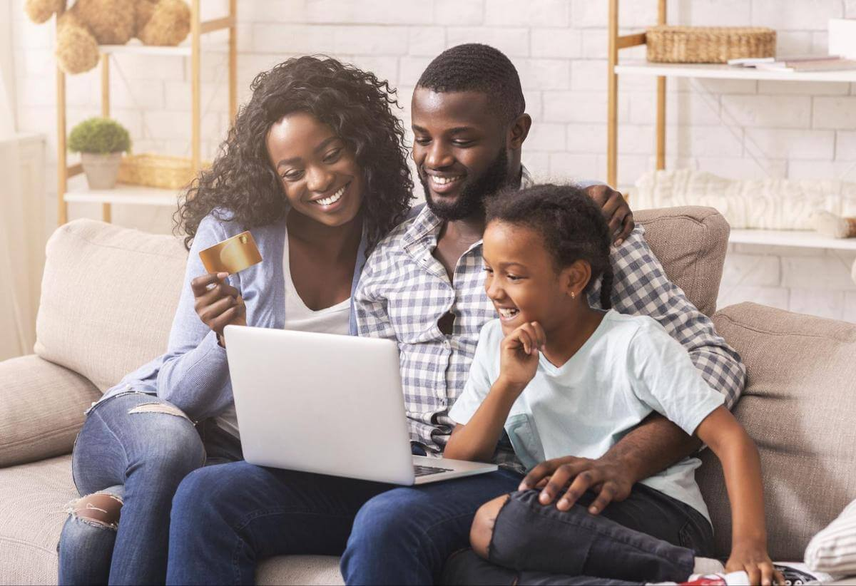 Can you have two debt consolidation loans: A smiling family holds a credit card while using a laptop