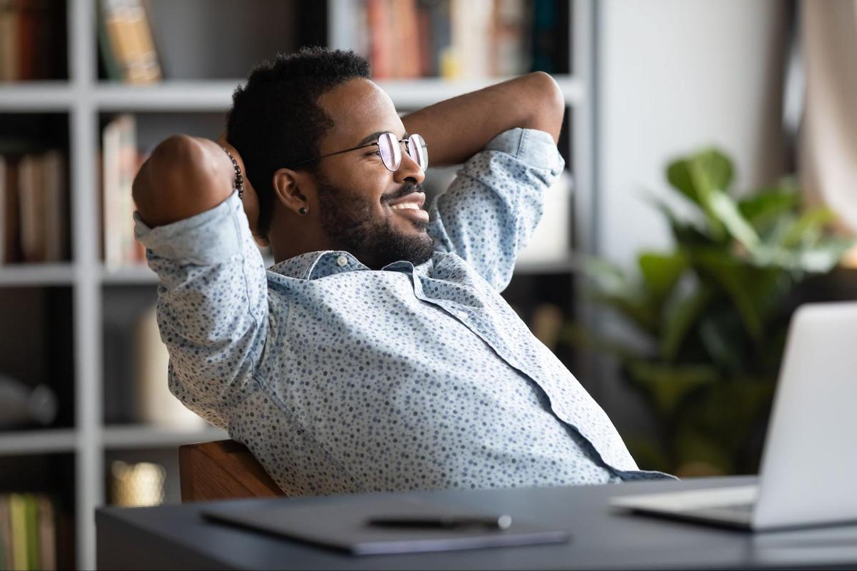 Difference between debt management and debt settlement: A man relaxes with his hands behind his head while sitting at a desk
