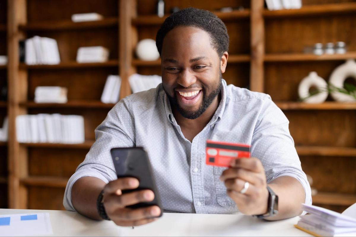 A smiling man uses his credit card on his mobile phone