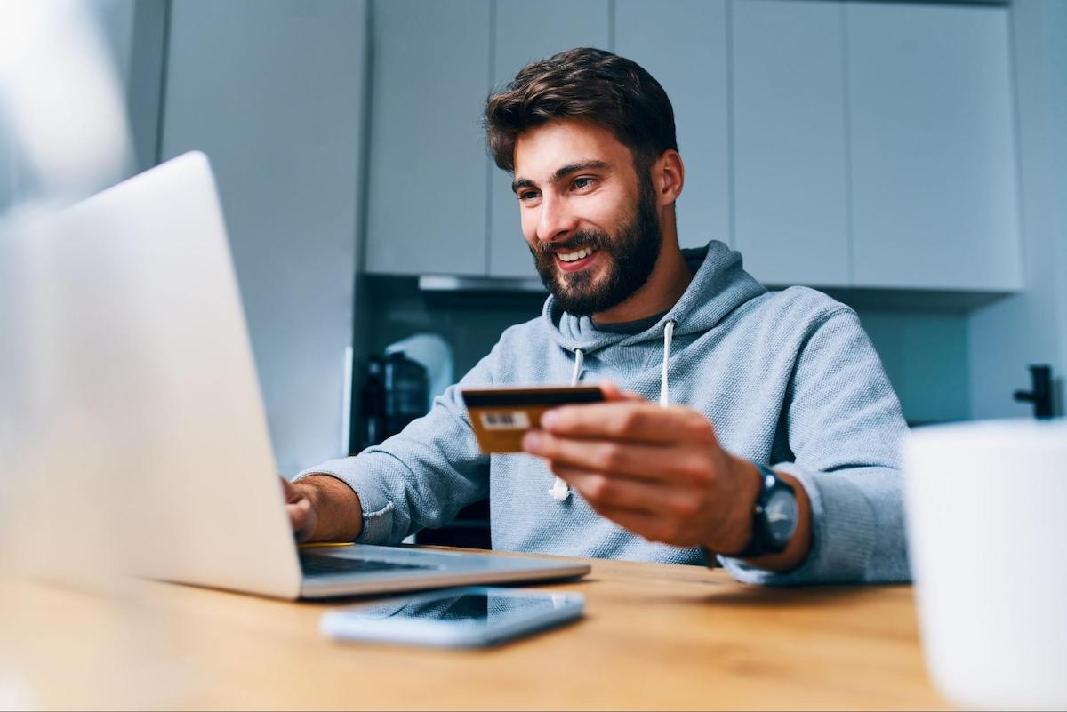 A man uses a credit card to make a purchase on his laptop