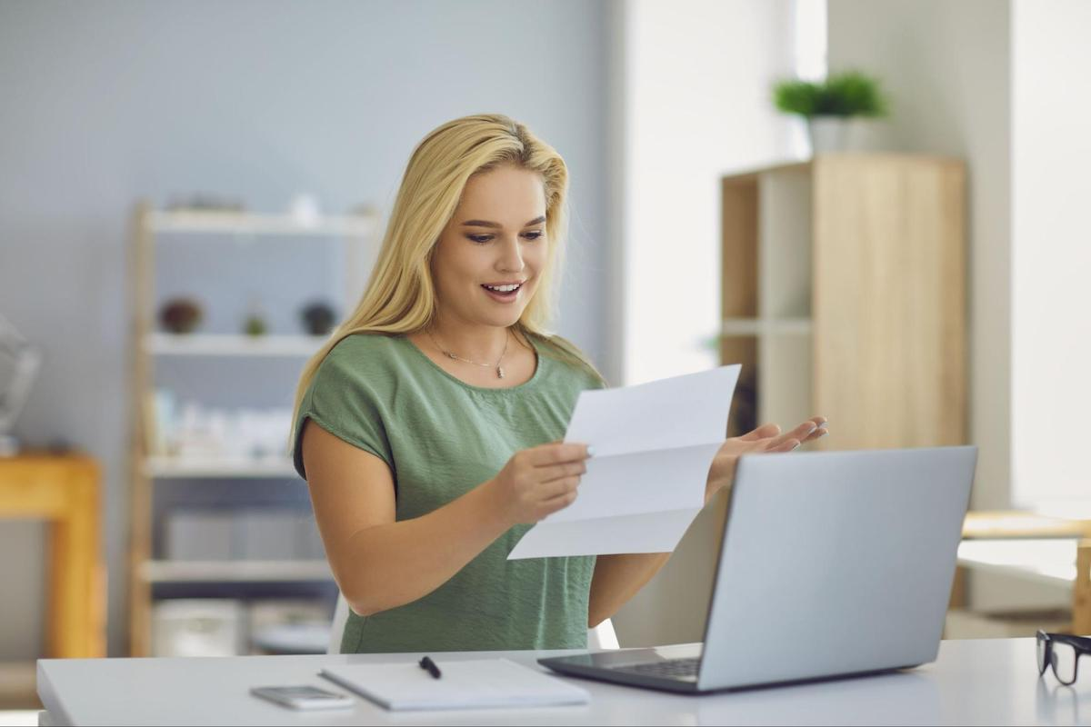 A smiling woman looks at a bill