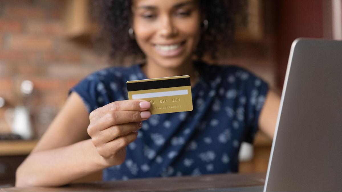 Should you refinance credit card debt: A smiling woman looks at her credit card