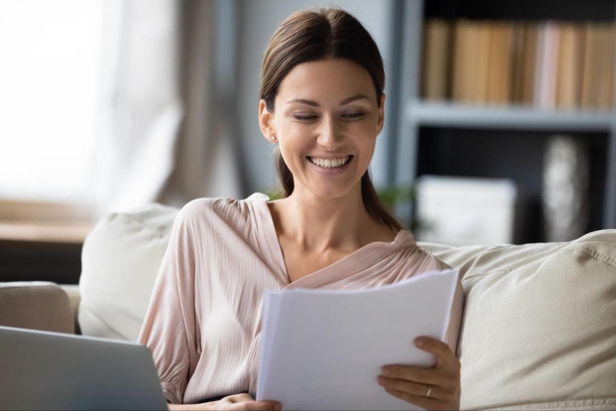 A smiling woman looks over her loan terms