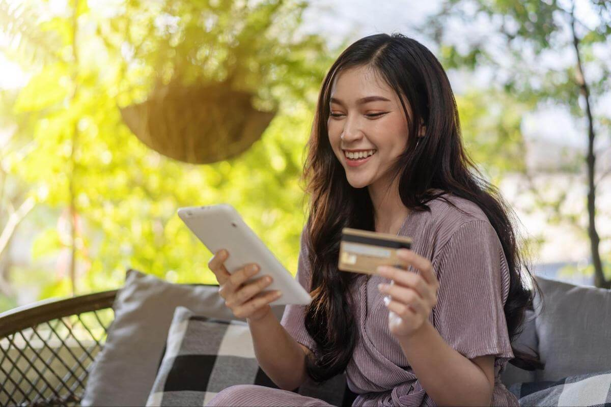 A smiling woman uses her credit card to make a purchase from a tablet