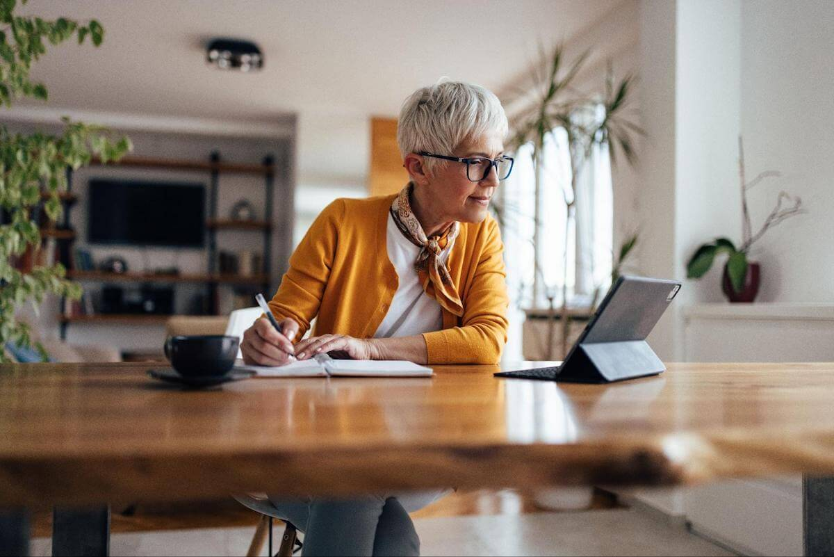 Can you refinance a credit card: A woman takes notes while using a tablet